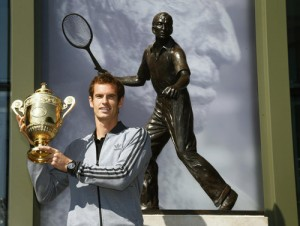 Tennis player Andy Murray of Britain holds the trophy under a statue of former British champion Fred Perry, at Wimbledon